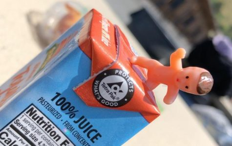 A plastic baby was found sitting on an orange juice box.