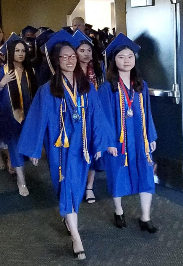 Anna+Chang+%28R%29%2C+Valedictorian%2C+and+Cecilia+Chak+%28L%29%2C+Salutatorian%2C+lead+the+class+of+2019+into+the+Richmond+Auditorium+for+the+graduation+ceremony.+